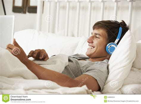 Teenage Boy Using Laptop And Headphones In Bed At Home