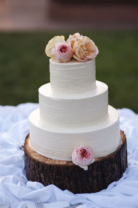 Simple White Wedding Cake On Wooden Log Cake Stand With