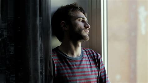 Portrait Of Handsome Young Sad Man In Front Of A Window