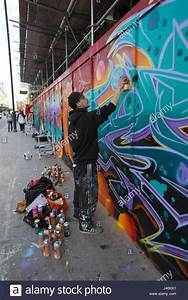 Street artist spray painting graffiti mural on hoarding ...