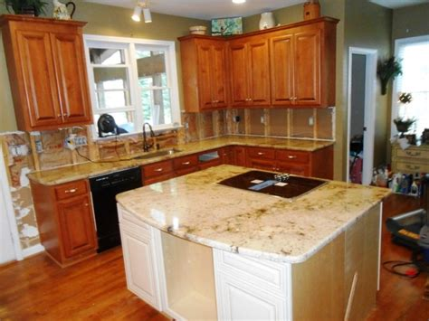 sienna beige granite  medium colored wood cabinets