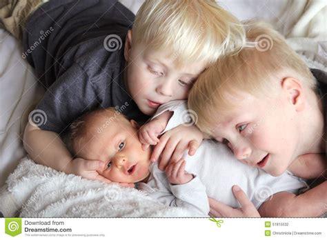 Big Brothers Hugging Newborn Baby Sister Stock Photo ...