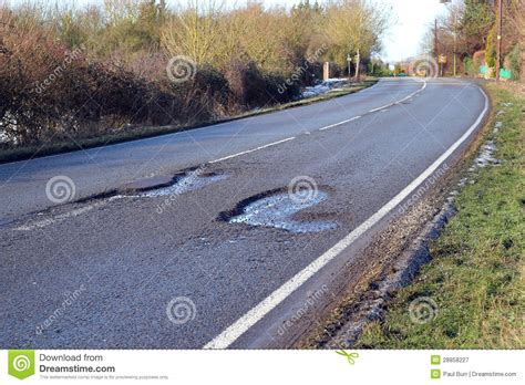Damaged Road With Pot Holes In It. Royalty Free Stock