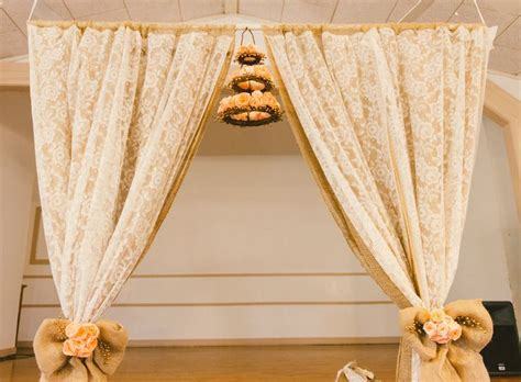 diy wedding arch lace curtains from thrift store and long layers of cheap burlap secured to