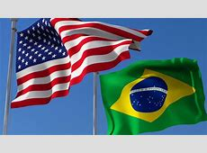 Flag Of Usa And Brazil Waving In The Wind Against Blue Sky