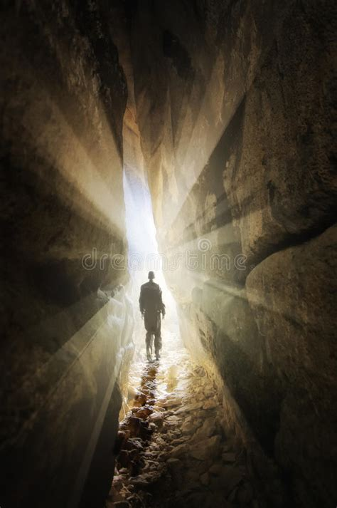 the cave and the light man walking out of a cave into the light stock image