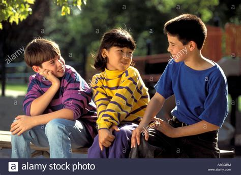 Three Children Of Different Nationalities Sitting On A