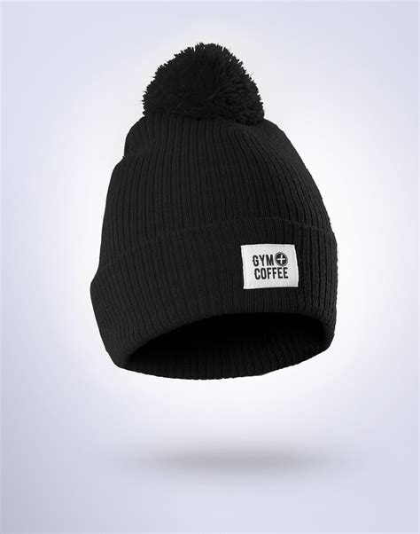Mockup of a barista wearing an apron while serving a drink. Black Bobble Unisex Beanie Hat | Gym+Coffee