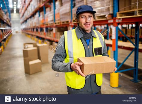 Warehouse Worker Holding A Small Box Stock Photo, Royalty