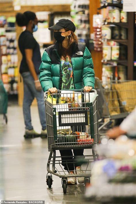 Emily Ratajkowski bundles up in a heavy green coat and ...