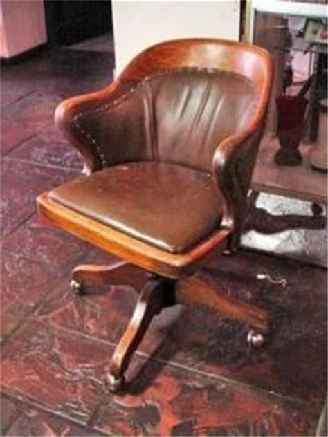antique wood and leather desk chair with brass tack finish