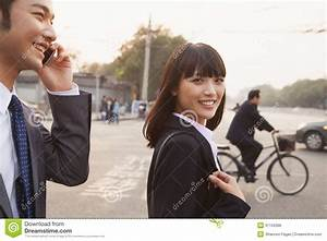 Two Smiling Young Business People Walking Outside On The ...