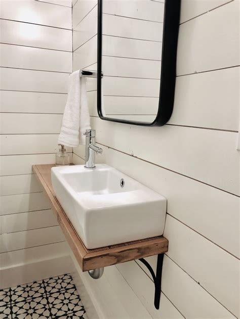 small powder room  shiplap walls cement floor tiles