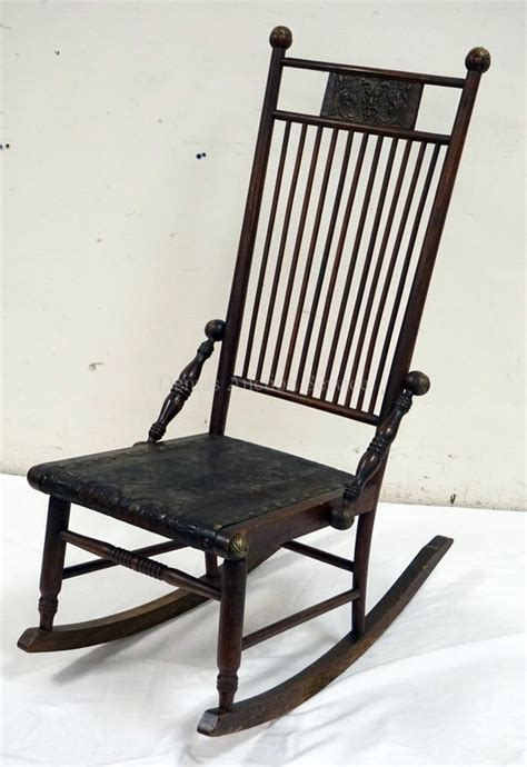 antique oak rocking chair with a tooled leather seat and bac
