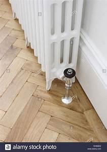 white radiator and herringbone parquet wooden flooring With parquet collant