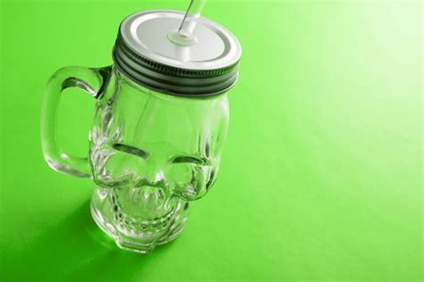 Image Of Empty Smiling Skull Glass Mug With Lid And Straw
