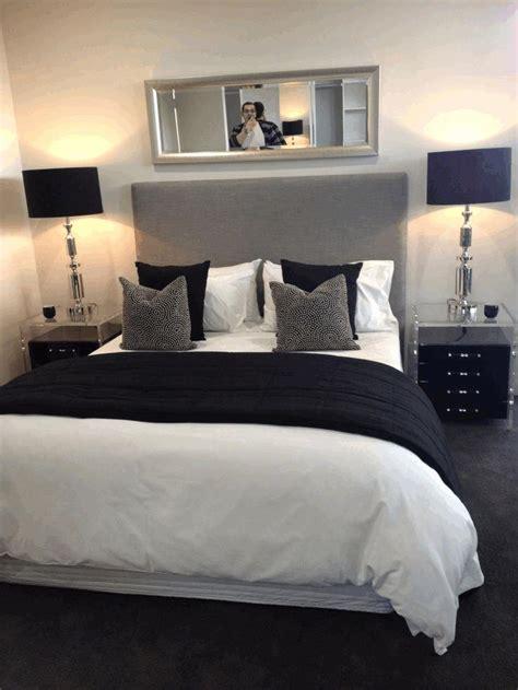 bedroom ideas white bed small furry gray pillows plain black carpet gray framed rectangular mirror gray and white