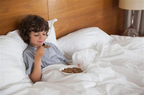 Young Boy Eating Breakfast In Bed Stock Photo
