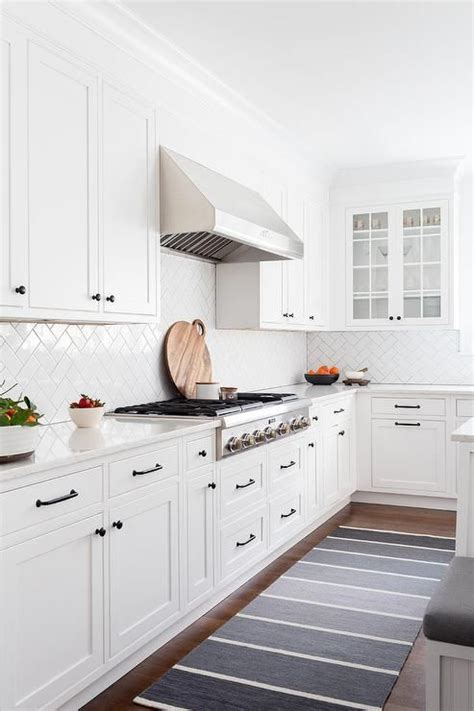 White Cabinets Bronze Hardware by A Gray Ombre Runner Sits In Front Of White Shaker Cabinets