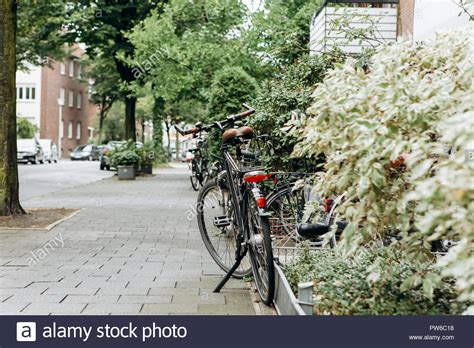 The Bike Is Parked Near The House On A Beautiful Street. Eco-friendly And Popular Transport In