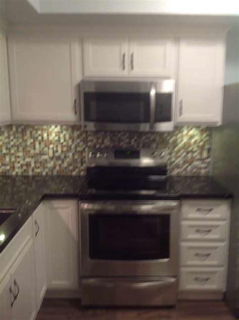 blue white kitchen  black granite countertop  stainless steel appliances