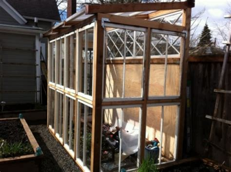 This charming little greenhouse is made from 4 window panels and 2 plywood panels. 14 DIY Greenhouses From Old Windows And Doors - Gardenoholic