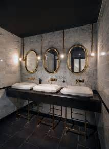 bathroom area with an industrial style brick style wall and metal frames on the mirror and