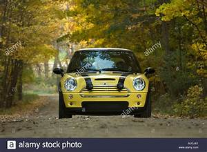 Yellow Mini Cooper S On A Rural Dirt Road In Autumn Stock