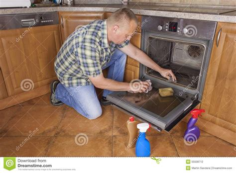 cleaning kitchen floor kneels on the floor in the kitchen and cleans the oven 2235