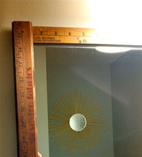 bathroom mirror with yardsticks framing bathroom mirror settlers