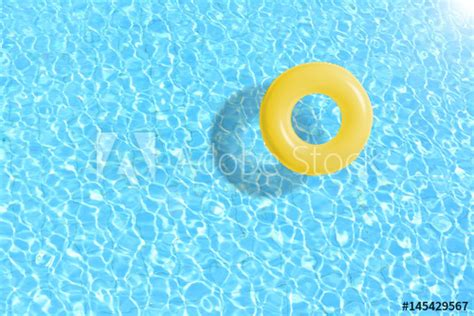 yellow swimming pool ring float  blue water concept
