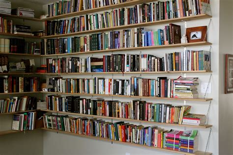 Brown Wooden Floating Ceiling Bookshelves On White Wall Of