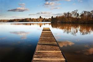 Landscape Of Fishing Jetty On Calm Lake At Sunset With