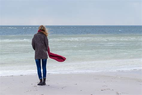 Lone Sad Beautiful Girl Walking Along The Shore Of The