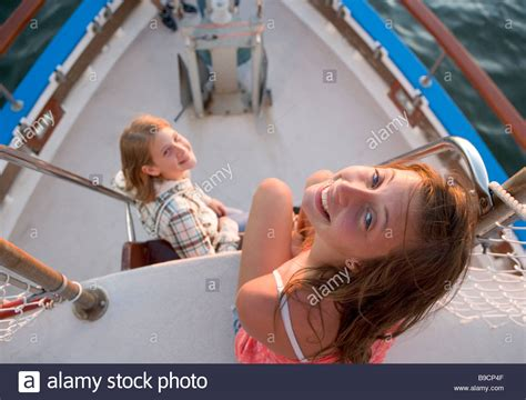 Girls On Boats by Two Teen Aged Girls Near The Bow Of A Tour Boat At Sunset