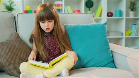Pretty Little Girl Reading Interesting Book While Sitting On The Couch In Lotus Position In The