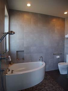 a, small, corner, soaking, tub, shares, a, compact, wet, room, with, a, shower, and, toilet
