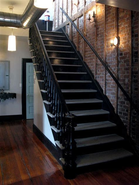 Black staircase, exposed brick wall, wood floors   Grown