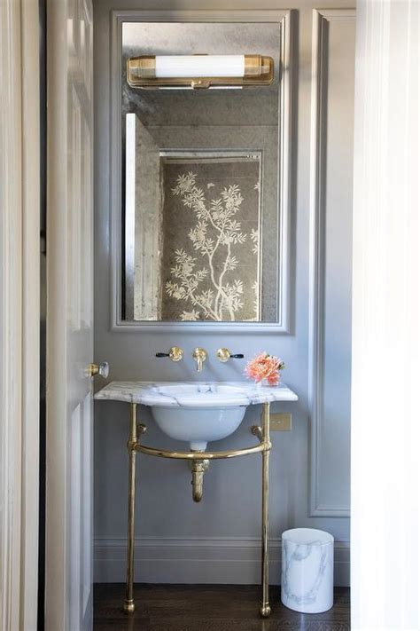 marble  brass sink vanity  gray wall french bathroom