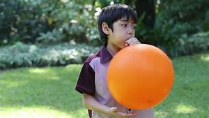 Stock video of little boy blowing a orange balloon ...  Blowing