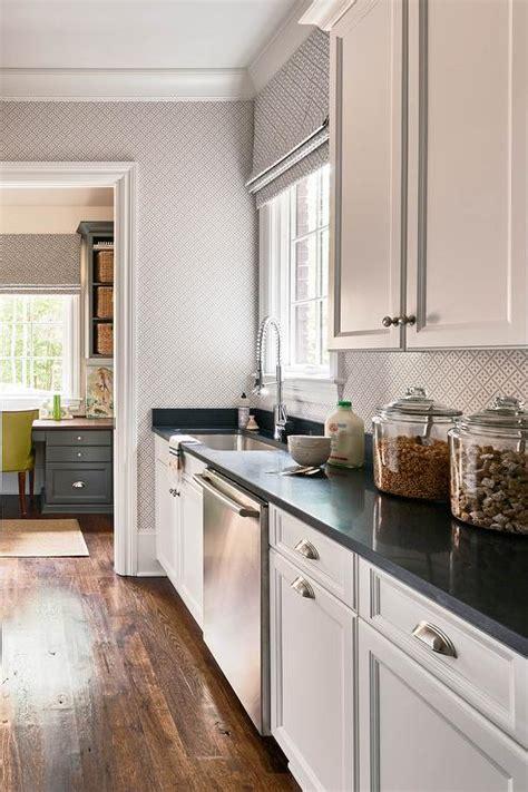 long kitchen pantry  white cabinets  black quartz