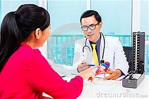 Asian Doctor With Patient In Medical Surgery Stock Photo ...