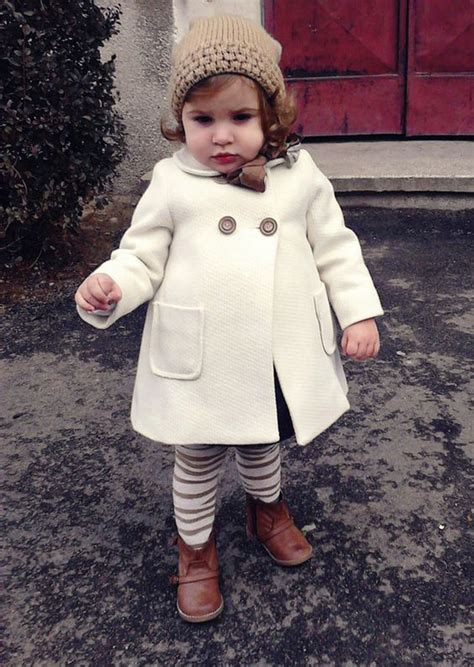Picture Of a white coat striped leggings a beanie and boots
