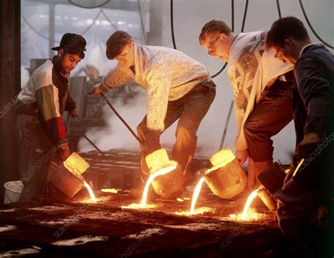 Foundry workers pouring hot metal into moulds - Stock ...