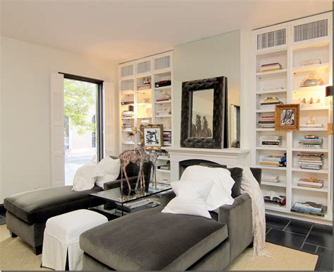 Chaise Lounge Chairs In Front Of Fireplace And Bookshelves