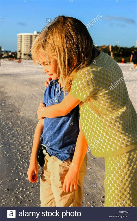 Young Pre Teen Sister Giving Her Younger Brother A Hug On