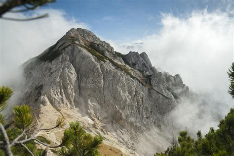 High Mountain In The Mist And Clouds Stock Photo