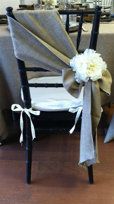 a simple burlap chair sash with a flower accent chair