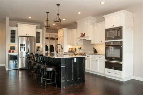 white kitchen with black island stacked moulding glazed kitchen cabinets white