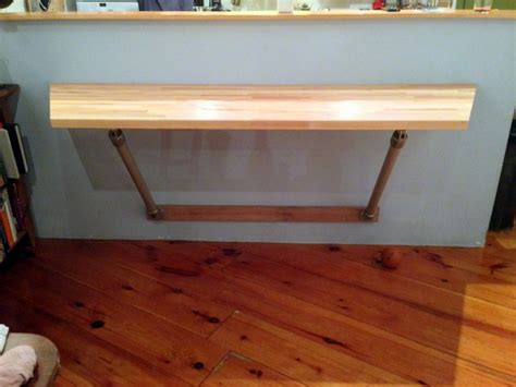 wall mounted butcher block table supported  pipe